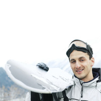 Man in warm clothing holding ski board