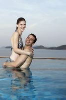 Man lifting up woman in swimming pool