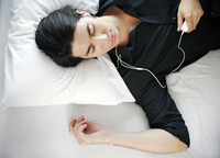 Man listening to music on the mp3 player while sleeping