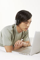 Man listening to music while using laptop