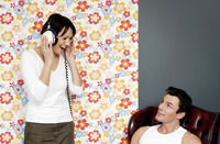 Man looking at his wife listening to music on the headphones