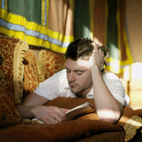 Man lying on the couch reading book