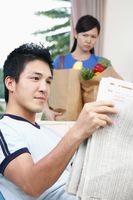 Man reading newspaper, woman carrying groceries in the background