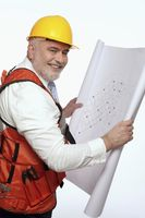 Man smiling while holding blueprint