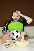 Man touching head with disappointment while watching football match at home