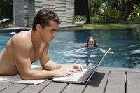 Man using laptop by the pool side, woman swimming in the pool