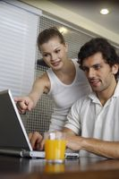 Man using laptop, woman pointing at laptop