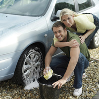 Man washing car wheel, woman hugging him from behind