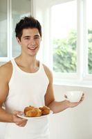 Man with a cup of coffee and a plate of croissants