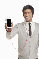 Man with earphone holding up a mobile phone