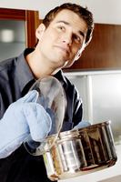 Man with oven mitt holding a pot of soup