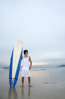 Man with sunglasses holding a surfboard on the beach