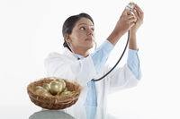 Medical personnel examining a golden egg