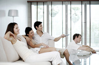 Men and women watching television at home