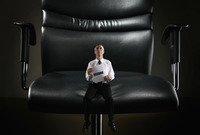 Mini sized businessman sitting on a giant chair holding resume