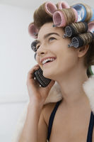 Model in curlers talking on cell phone