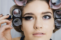 Model in hair curlers applying mascara