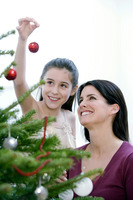 Mother and daughter decorating the christmas tree