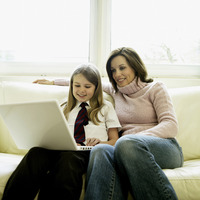 Mother and daughter sitting on the couch using laptop