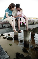 Parents and daughter sitting at the pier