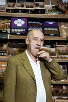 Portrait of a mature man smoking cigar in tobacco store