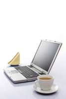 Sandwich and a cup of tea beside a laptop