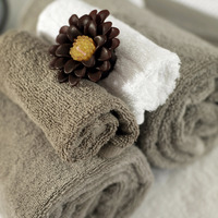 Scented candle on rolled up towels