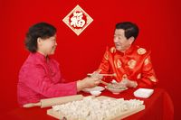 Senior man and woman making chinese dumplings