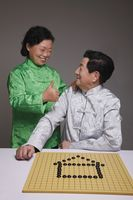 Senior man arranging black pebbles into a house, senior woman showing him thumbs up
