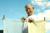 Senior man hanging laundry on washing line