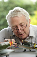 Senior man painting model airplane