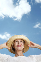 Senior woman smiling while holding her hat