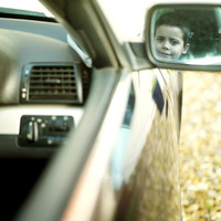 Side mirror reflection of boy sitting in the car