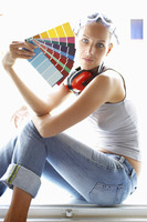 Side shot of a woman with headphone and goggles holding colour cards