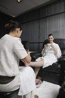 Spa attendant massaging a woman's foot