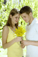Teenage boy giving his girlfriend a bouquet of flowers