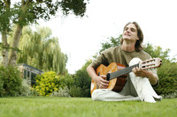 Teenage boy sitting on the field playing guitar