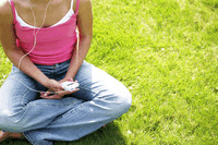 Teenage girl sitting on the field listening to music on a portable mp3 player