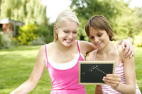 Teenage girls looking at photo in photo frame