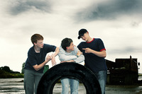 Three boys posing with a big tyre
