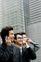 Three businessmen talking on the hand phone