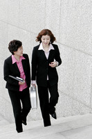 Two business women chatting while walking up the stairs