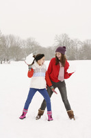 Two girls playing with snowballs