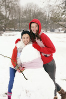 Two girls posing with snowman
