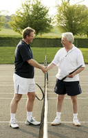 Two men shaking hands in a tennis court