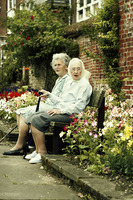 Two old women sitting on the bench together