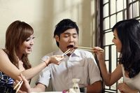 Two women feeding man with grilled beef