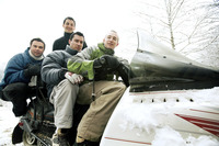 Winter sport players posing on snowmobile