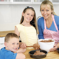 Woman and girl baking in the kitchen, boy smiling at the camera