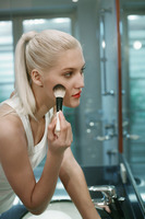 Woman applying blusher in the bathroom